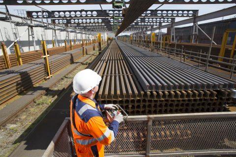 Orange saftey suited engineer inspects stockpile of new rails at British Steel works in UK